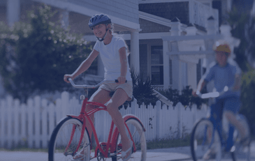 Image of girl riding on a bike in suburban neighborhood